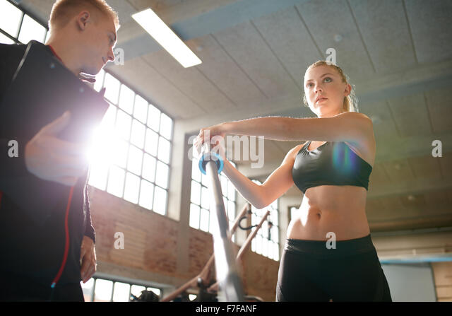 Shot of a young woman exercising in the gym. Female using fitness equipment with the supervision of a personal trainer. - Stock Image