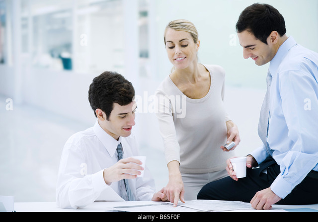 Three professionals taking a coffee break, woman pointing at newspaper - Stock-Bilder