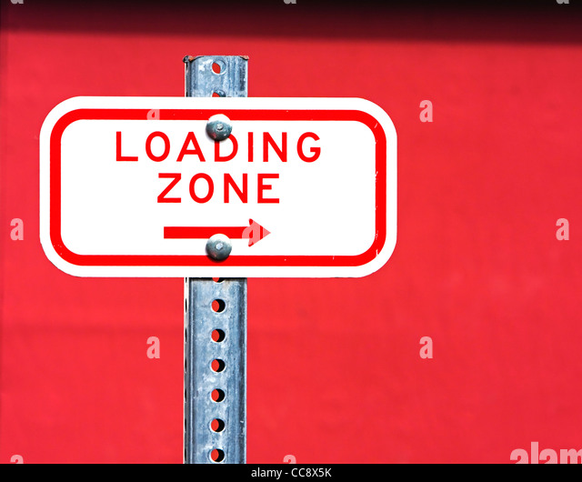 loading zone sign against red wall - Stock Image