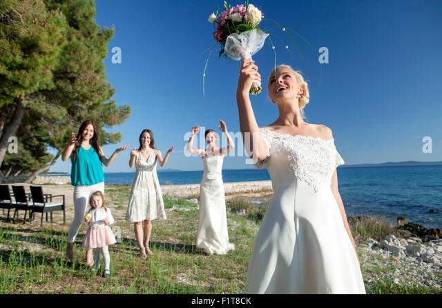 Bride throwing bouquet at wedding reception - Stock Image