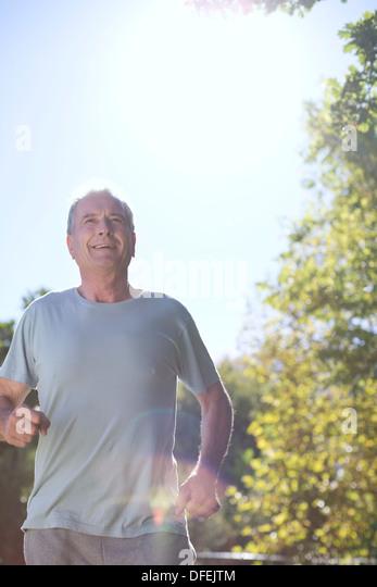 Senior man running outdoors - Stock Image