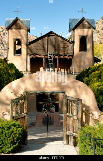 Adobe gate and Santuario de Chimayo, Chimayo, New Mexico USA - Stock Image