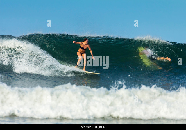 Girl surfer riding wave at popular Playa Guiones surf beach, Nosara, Nicoya Peninsula, Guanacaste Province, Costa - Stock-Bilder