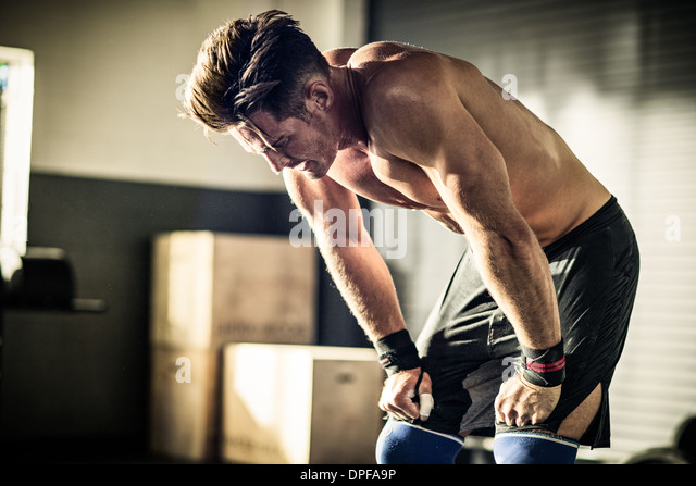 Young man bending forward with exhaustion in gymnasium - Stock Image