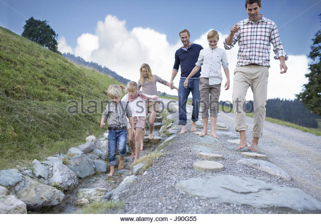 Father And Children On Countryside Path Next To Stream - Stock-Bilder