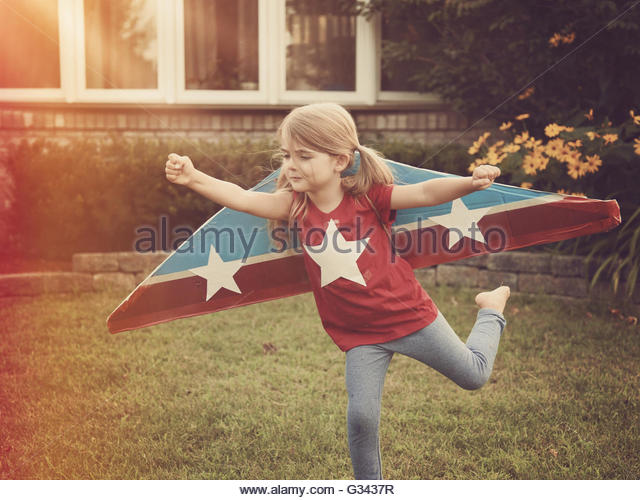 A child is wearing cardboard flying wings with stars on them pretending to be a pilot for a craft, imagination, - Stock Image