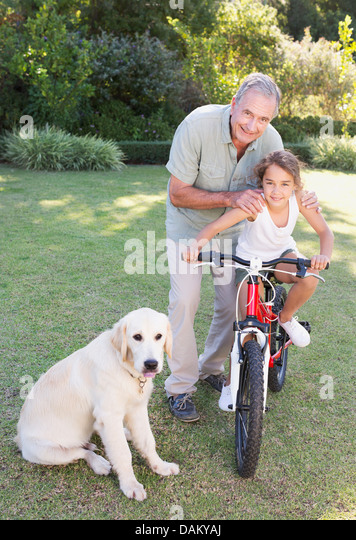 Older man with granddaughter and dog - Stock Image