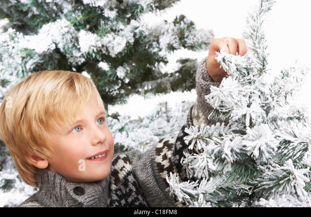 Boy decorating the Christmas tree - Stock Image