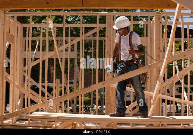 Carpenter standing at a construction site holding a nail gun - Stock-Bilder
