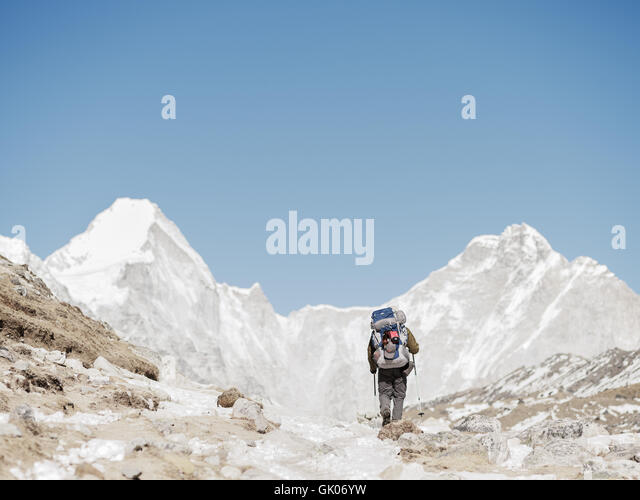 A hikers makes his way through the snow covered Himalayas on his Everest Base Camp journey - Stock Image