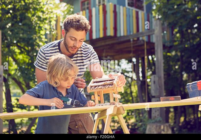 Father and son doing woodwork together, outdoors - Stock Image