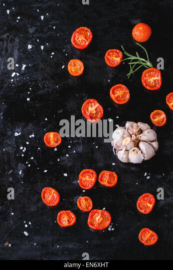Sun-dryed cherry tomatoes and garlic with rosemary and sea salt over black metal oven-tray. Top view - Stock Image