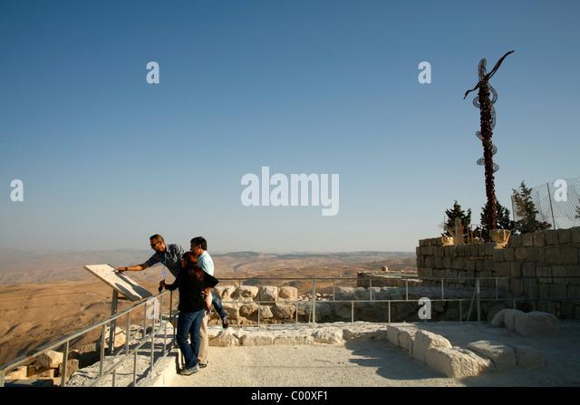 Tourists at Mount Nebo with the memorial cross behind, Jordan. - Stock-Bilder