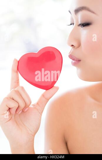 MODEL RELEASED. Young Asian woman holding heart, portrait. - Stock-Bilder