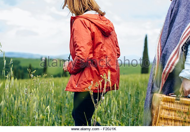 Cropped shot of two mature women strolling in wheatfield, Tuscany, Italy - Stock Image