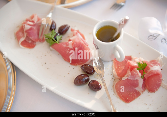 Germany, Garnished ham, olives with olive oil on tray - Stock Image