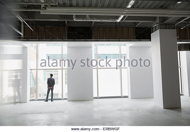 Businessman at window of empty office space - Stock Image