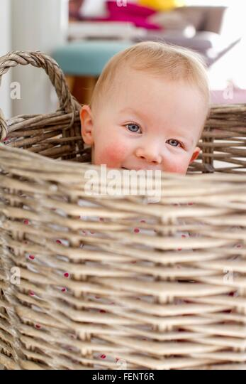 Portrait of cute female toddler hiding in wicker basket - Stock Image