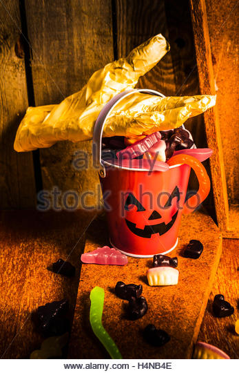 Creepy halloween still life photo on a invisible mummy collecting a Jack o Lantern candy bucket overfilled with - Stock Image