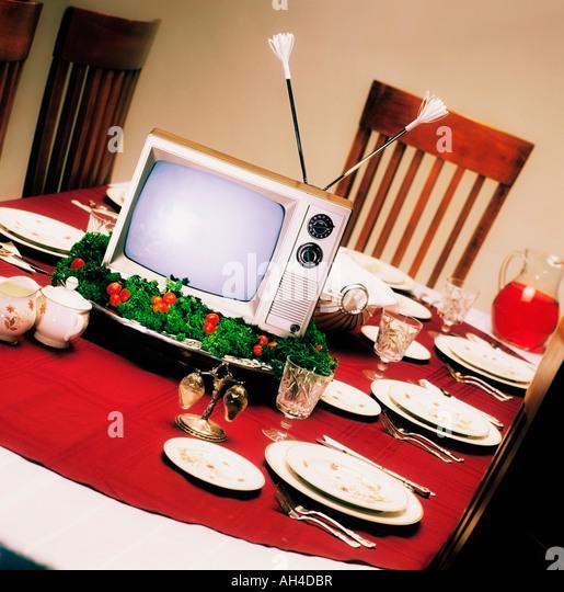 TV on platter on dinner table - Stock Image