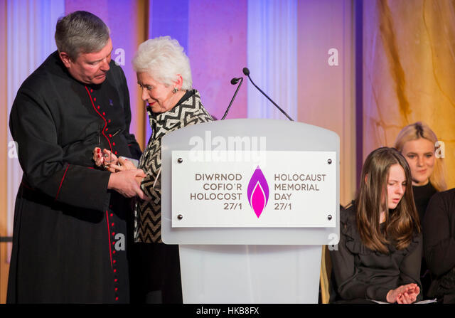 Cardiff, Wales, Uk. 27th Jan, 2017.  Holocaust survivor Eva Clarke is supported by The Reverend Canon Stewart Lisk - Stock Image