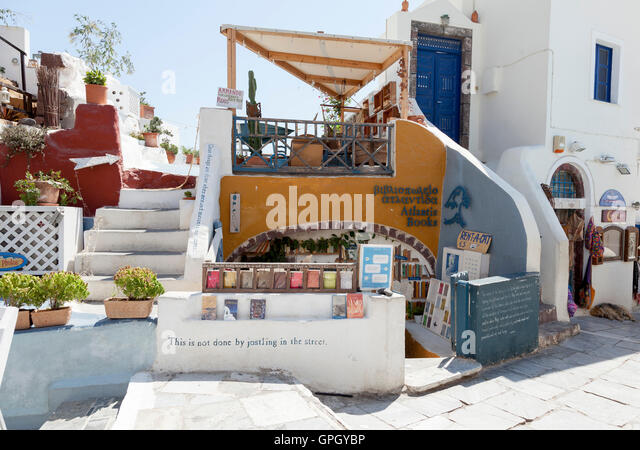 The remarkable Atlantis Bookshop in the busy and popular town of Oia on the Greek island of Santorini. This is the - Stock Image