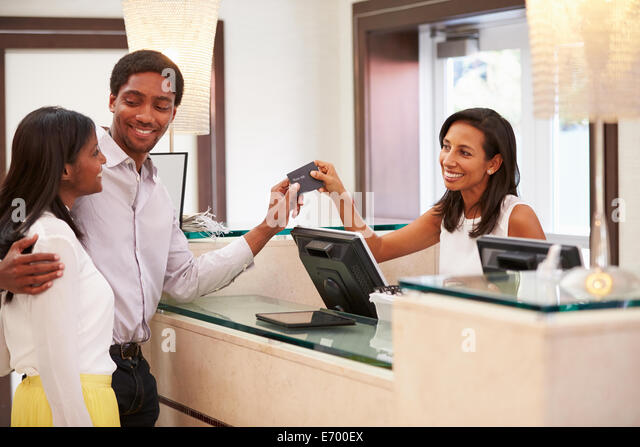 Couple Checking In At Hotel Reception - Stock Image