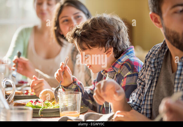 A group of people, adults and children, seated around a table for a meal. - Stock Image