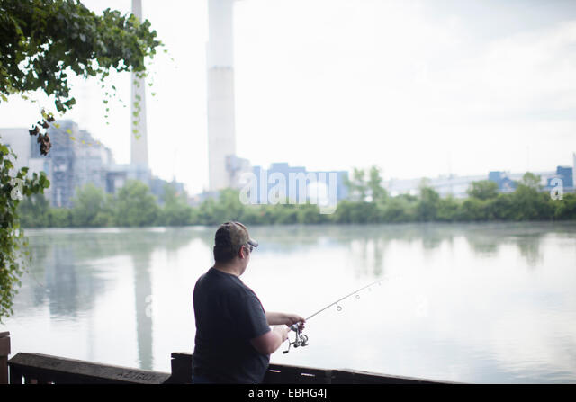 Man fishing opposite Detroit Edison Power Station, river Raisin, Monroe, Michigan, USA - Stock Image