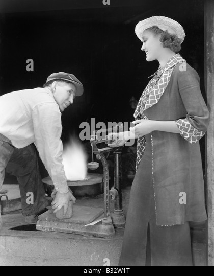 Woman weighing a piece of iron at a foundry - Stock Image