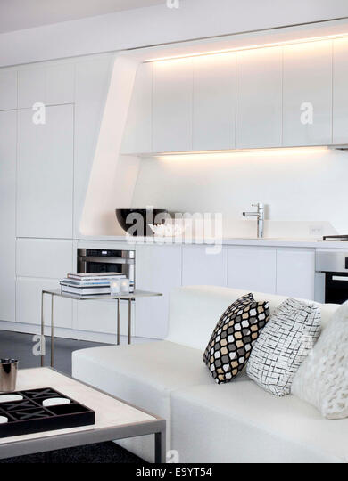 all white couch and kitchen in loft apartment - Stock-Bilder