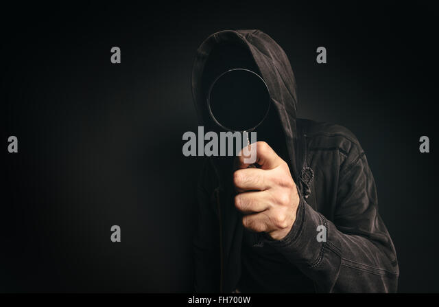 Spyware computer software, hooded spooky person with magnifying glass peeking at you - Stock Image