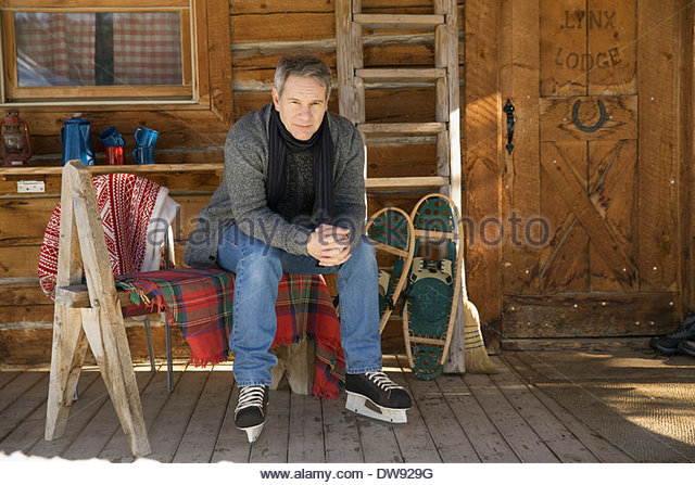 Man sitting outside of cabin wearing ice skates - Stock Image