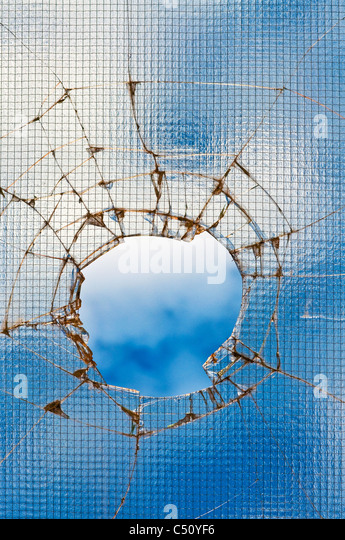 Broken glass - cracked with hole over blue sky. - Stock Image