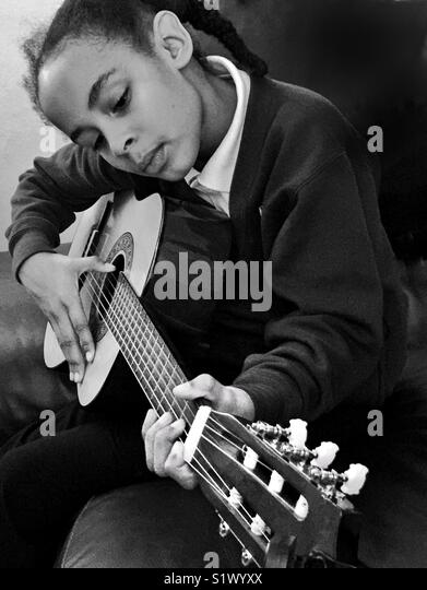 A young girl playing a guitar. - Stock Image