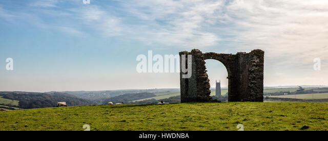 Stoke Barton church tower seen through the arch of ruined Pleasure House Folly on the cliffs above Hartland Quay - Stock Image
