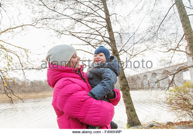 Sweden, Stockholm, Sodermalm, Woman carrying baby (12-17 months) - Stock Image
