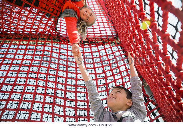Girl lifting helping boy climb rope net - Stock Image