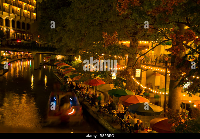San Antonio River Walk riverwalk above at night tour boat and outdoor cafes lining the riverbank - Stock Image