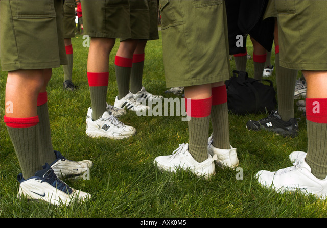 young student people peformers in uniform legs feet white shorts shooes socks green red stripe grass ground dirt - Stock Image