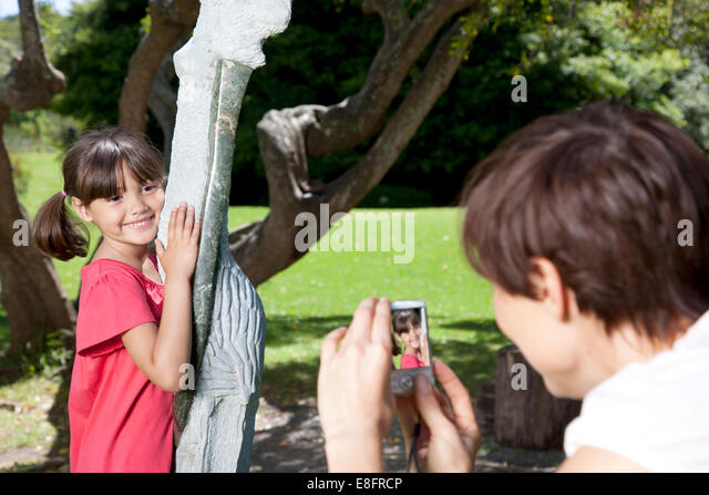 Mother taking photograph of child in park - Stock Image
