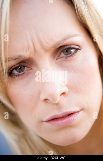 Head shot of woman scowling - Stock Image