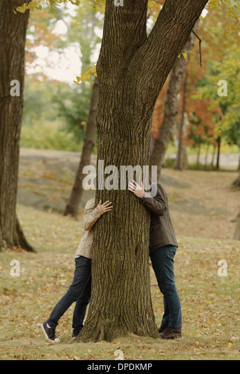 Gay couple hiding head behind tree trunk - Stock Image