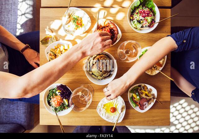 Directly above shot of couple eating meze at Lebanese restaurant - Stock-Bilder