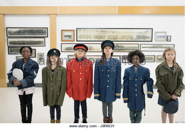 Portrait multi-ethnic students wearing military uniforms in war museum - Stock-Bilder