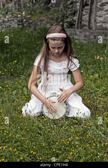 a girl sitting in a meadow and plays Djembe - Stock-Bilder