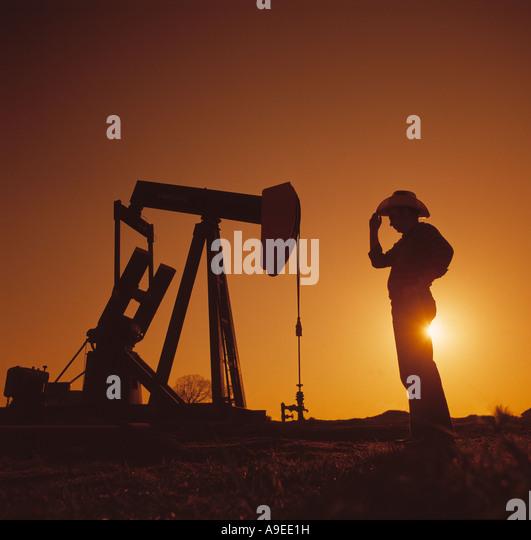 Man and an oil field pump jack - Stock-Bilder