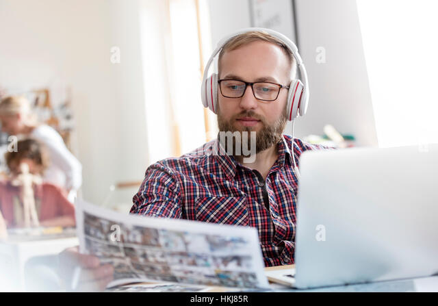 Design professional listening to music with headphones reviewing proofs at laptop - Stock-Bilder