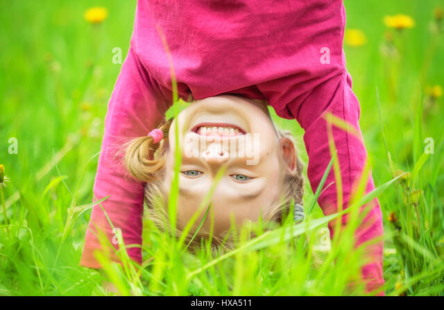 Happy little girl standing upside down on grass in summer park - Stock Image