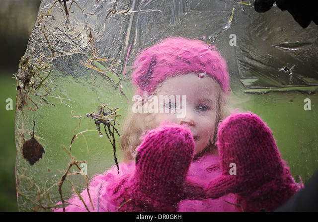 Little girl looking through ice sheet with pink gloves on - Stock Image